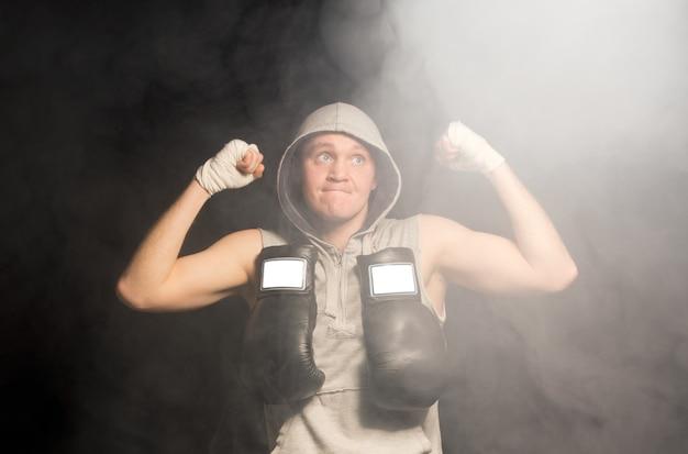 Zdeterminowany młody bokser wznoszący wysoko pięści