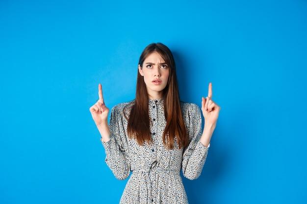 Zdezorientowana atrakcyjna kobieta w sukni marszcząca brwi, wskazująca palcami w górę i wyglądająca na zdziwioną, nie może czegoś zrozumieć, wpatruje się w dziwną rzecz, niebieską.