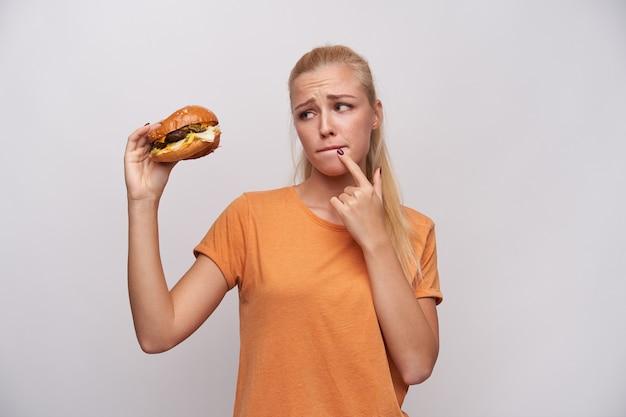 Zdezorientowana atrakcyjna młoda blondynka w codziennych ubraniach marszczy brwi i gryzie usta, patrząc na dużego burgera w dłoni, licząc kalorie i wątpiąc, na białym tle