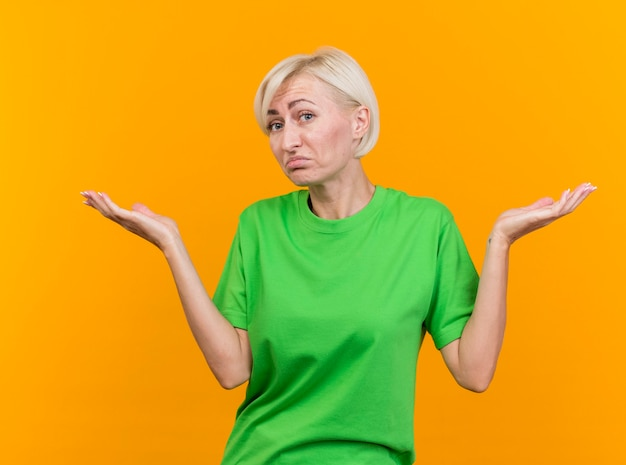 Zdezorientowana blondynka w średnim wieku patrząc na przód robi nie wiem gest na białym tle na żółtej ścianie