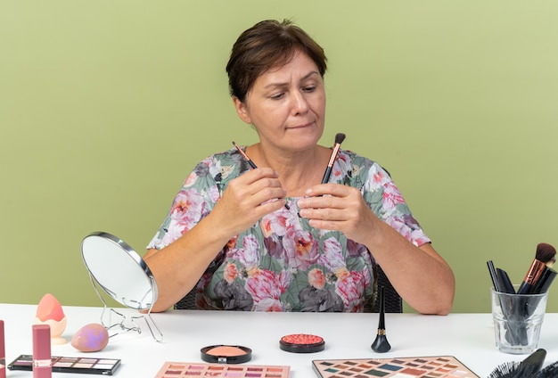Zdezorientowana dorosła kaukaska kobieta siedzi przy stole z narzędziami do makijażu, trzymając i patrząc na pędzle do makijażu izolowane na oliwkowozielonej ścianie z kopią przestrzeni
