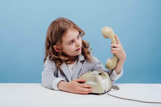 Zdezorientowana dziewczynka ze starym telefonem siedząca przy stole na niebieskim tle