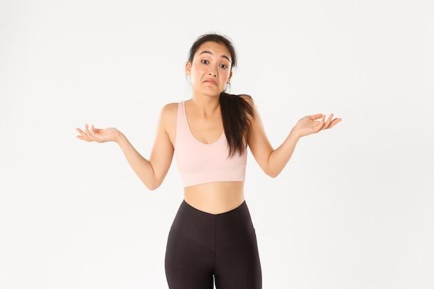 Zdezorientowana i nieświadoma azjatycka dziewczyna fitness, atletka w odzieży sportowej nie wiem, wzrusza ramionami i krzywi się zdziwiona, stojąc nieświadomie na białym tle.