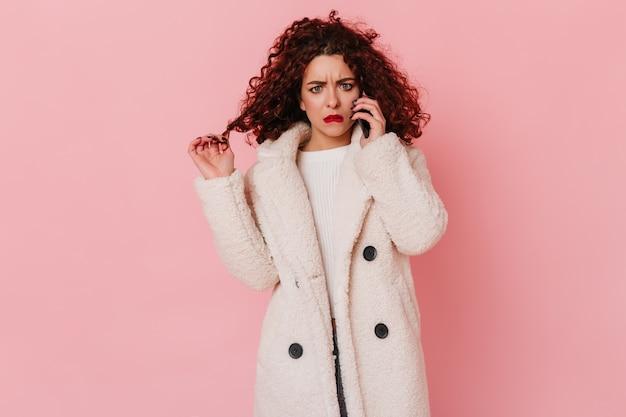 Zdezorientowana i smutna dziewczyna z czerwonymi ustami rozmawia przez telefon. portret kobiety w płaszcz ekologiczny na różowej przestrzeni.