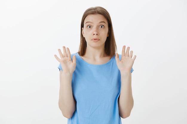 Zdezorientowana i zaskoczona kobieta unosząca ręce w geście poddania się, niechętna do udziału