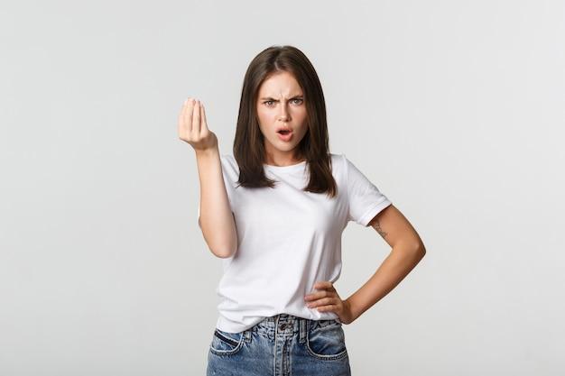 Zdezorientowana i zła brunetka dziewczyna kłóci się o pieniądze.