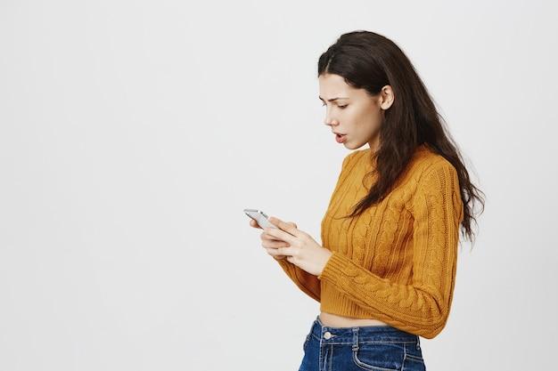 Zdezorientowana i zmartwiona dziewczyna patrząc na telefon komórkowy z sfrustrowaną twarzą