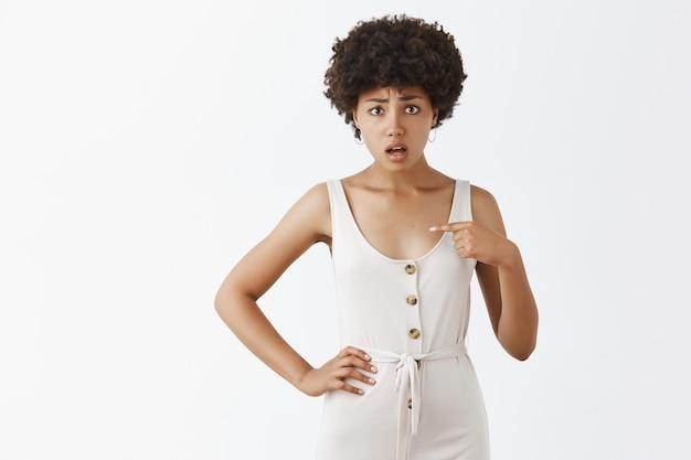 Zdezorientowana i zmartwiona stylowa dziewczyna pozuje przy białej ścianie