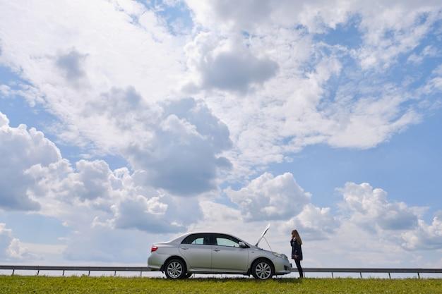 Zdezorientowana kobieta czeka na pomoc w pobliżu zepsutego samochodu z otwartą maską, stoi na poboczu drogi