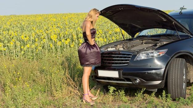 Zdezorientowana kobieta stojąca patrząc na komorę silnika swojego samochodu, który zepsuł się obok pola słoneczników na wsi