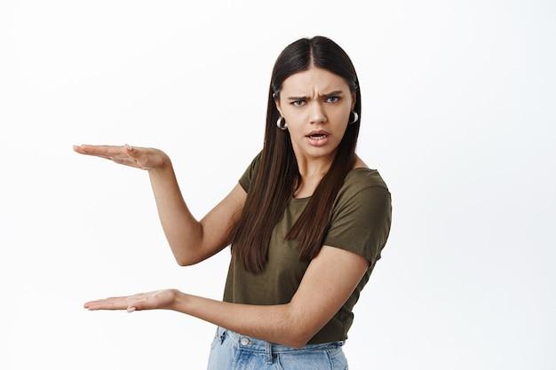 Zdezorientowana kobieta trzymająca pustą przestrzeń na logo lub baner, pokazująca gest dużego pudełka i patrząca zdziwiona z przodu, stojąca na białej ścianie