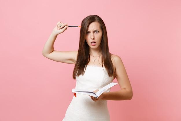 Zdezorientowana kobieta w białej sukni szukająca pomysłów pisania notatek w notatniku pamiętnika