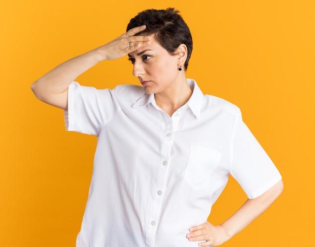 Zdezorientowana kobieta w średnim wieku trzymająca ręce w talii i na głowie, patrząc z boku