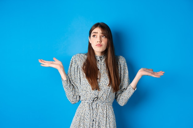 Zdezorientowana ładna dziewczyna w sukience wzrusza ramionami i patrzy na bok smutno, nic nie wie, stojąc na tle błękitu.