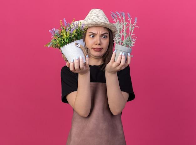 Zdezorientowana ładna kaukaska ogrodniczka w kapeluszu ogrodniczym trzymająca doniczki