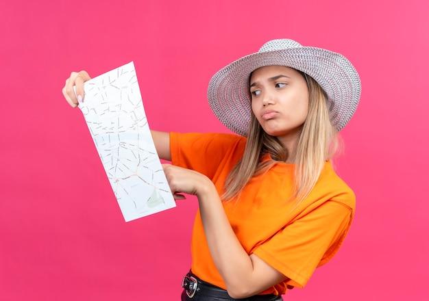 Zdezorientowana, ładna młoda kobieta w pomarańczowym t-shircie w kapeluszu przeciwsłonecznym, trzyma mapę i patrzy na nią na różowej ścianie