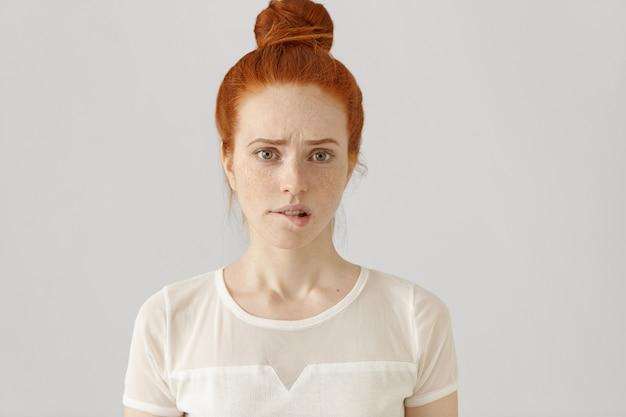 Zdezorientowana lub zdziwiona piękna młoda kobieta rasy białej z marszczonymi brwiami rudymi włosami