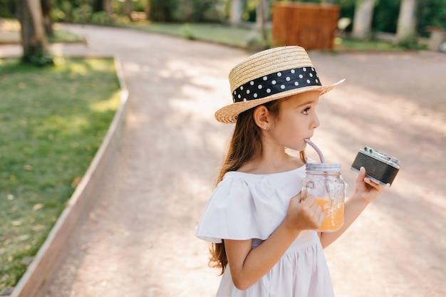 Zdezorientowana mała dama w łodzi ze słomy, trzymając aparat na ulicy i odwracając wzrok. zewnątrz portret śliczna ciemnowłosa dziewczyna ze szklanką soku pomarańczowego idąc alejką.