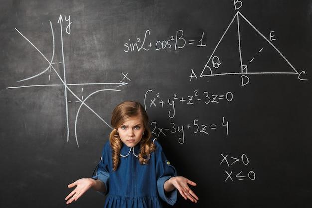 Zdezorientowana mała uczennica stojąca przy tablicy z napisaną grafiką matematyczną