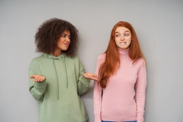 Zdezorientowana młoda atrakcyjna brązowowłosa, kręcona ciemnoskóra kobieta marszczy brwi i unosi zmieszane ręce, pozując na szarej ścianie ze zdziwioną rudowłosą ładną kobietą