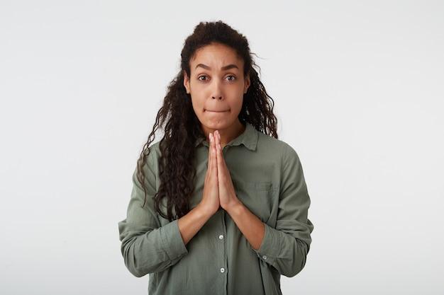 Zdezorientowana młoda atrakcyjna, długowłosa, kręcona, ciemnoskóra kobieta z naturalnym makijażem podnosząca ręce w geście modlitwy i niepokojąco gryząca usta, pozując na białym tle