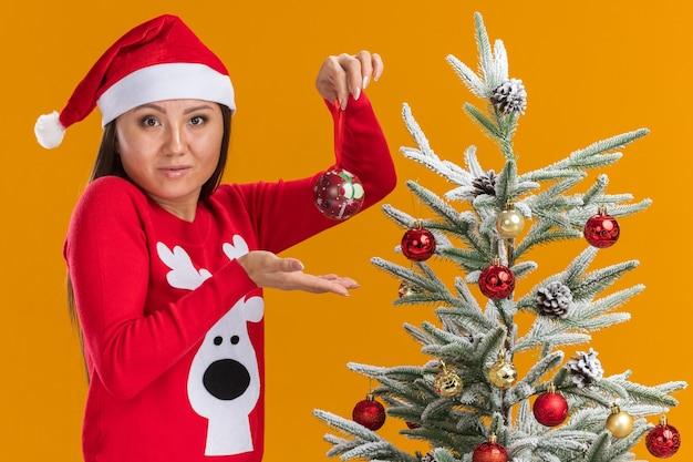 Zdezorientowana młoda azjatycka dziewczyna ubrana w świąteczny kapelusz ze swetrem stojąca w pobliżu choinki trzymając kulki choinkowe odizolowane na pomarańczowej ścianie