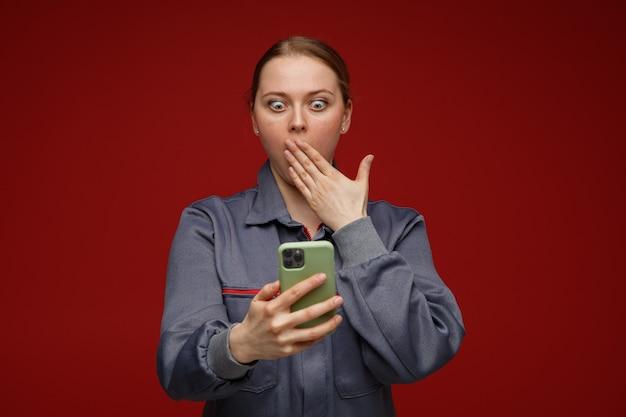 Zdezorientowana młoda blond inżynier kobieta ubrana w mundur trzymając i patrząc na telefon komórkowy robi gest ups
