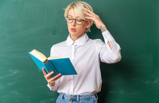 Zdezorientowana młoda blond nauczycielka w okularach w klasie, stojąc przed tablicą, trzymając i czytając książkę, dotykając głowy