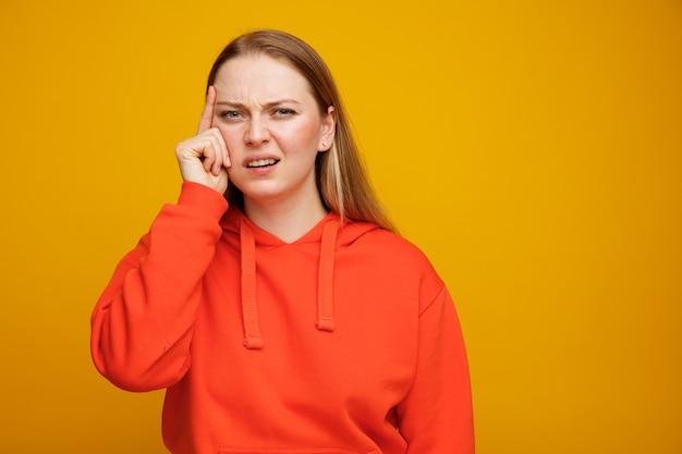 Zdezorientowana młoda blondynki kobieta robi gest myślenia