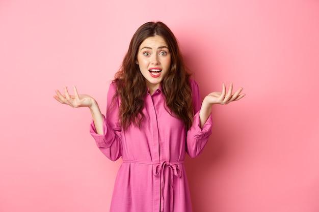 Zdezorientowana młoda brunetka z nerwowym wyrazem twarzy, podnosząca ręce do góry i wzruszająca ramionami, nie wiem, nie rozumiem, stoi nad różową ścianą.