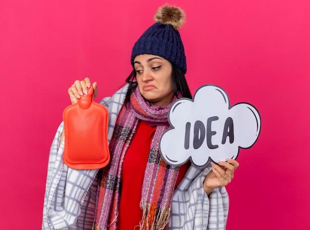 Zdezorientowana młoda chora kobieta w czapce zimowej i szaliku owinięta w kratę, trzymająca bańkę pomysłu i torbę z gorącą wodą, patrząc na torbę z gorącą wodą odizolowaną na różowej ścianie