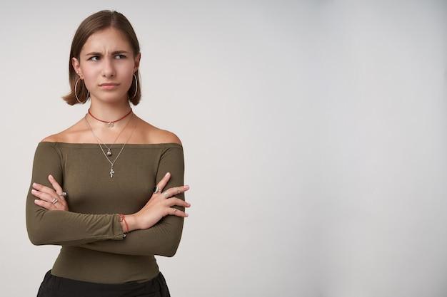 Zdezorientowana młoda ciemnowłosa dama z krótkimi fryzurami i złożonymi rękami na piersi, patrząc zmieszana na bok, ubrana w oliwkową bluzkę, pozując na białej ścianie