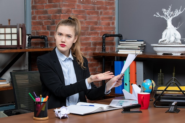 Zdezorientowana młoda dama siedzi przy stole i pokazuje dokument w biurze