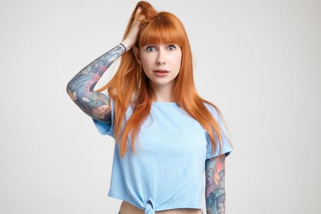 Zdezorientowana młoda, dość długowłosa ruda dama ubrana w niebieską koszulkę trzymająca podniesioną rękę na głowie, patrząc zdumiony na aparat, odizolowana na białym tle