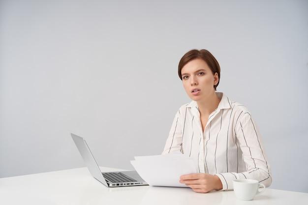Zdezorientowana młoda dość krótkowłosa brunetka dama z naturalnym makijażem siedzi przy stole na białym tle i trzyma kartkę papieru, mrużąc oczy z poważną twarzą