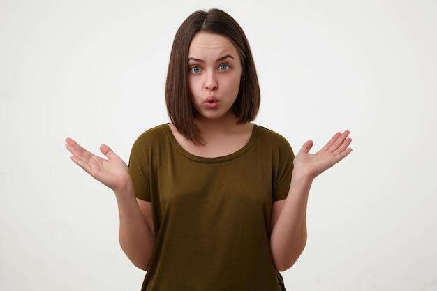 Zdezorientowana młoda, dość krótkowłosa brunetka kobieta podnosi zmieszane ręce i wydyma wargi, patrząc na kamery, odizolowana na białym tle