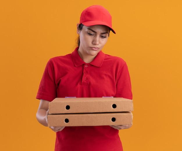 Zdezorientowana młoda dziewczyna dostawy ubrana w mundur i czapkę, trzymając i patrząc na pudełka po pizzy na białym tle na pomarańczowej ścianie