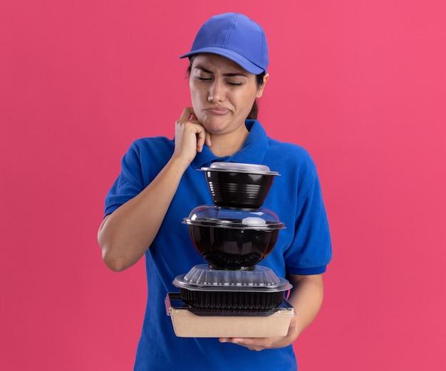 Zdezorientowana młoda dziewczyna dostawy ubrana w mundur z czapką, trzymając i patrząc na pojemniki na żywność drapiąc policzek na białym tle na różowej ścianie