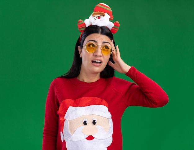 Zdezorientowana młoda dziewczyna kaukaska ubrana w opaskę świętego mikołaja i sweter w okularach, patrząc w górę dotykając głowy na białym tle na zielonym tle