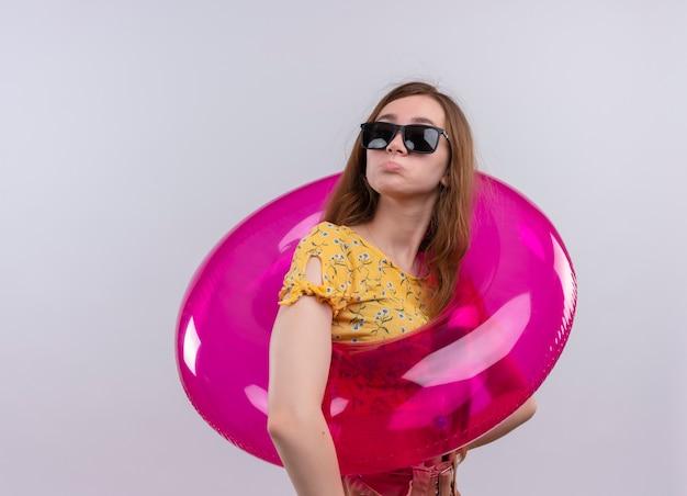 Zdezorientowana młoda dziewczyna nosi okulary przeciwsłoneczne i pierścień do pływania na odosobnionej białej przestrzeni z miejsca na kopię