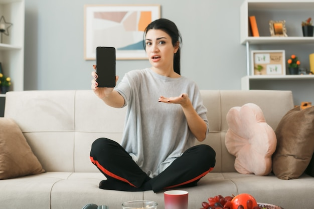 Zdezorientowana młoda dziewczyna trzyma i wskazuje ręką przy telefonie, siedząc na kanapie za stolikiem kawowym w salonie