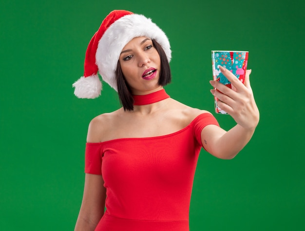 Zdezorientowana młoda dziewczyna ubrana w santa hat wyciągając plastikowy kubek bożonarodzeniowy patrząc na niego na białym tle na zielonej ścianie