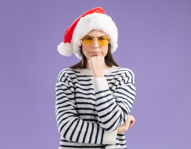 Zdezorientowana młoda kaukaska dziewczyna w okularach przeciwsłonecznych z czapką mikołaja trzyma podbródek i wygląda