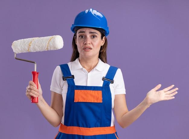Zdezorientowana młoda kobieta budowniczy w mundurze, trzymając pędzel rolkowy i rozkładając rękę na białym tle na fioletowej ścianie