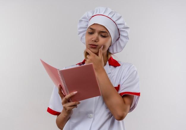 Zdezorientowana młoda kobieta kucharz ubrana w mundur szefa kuchni patrząc na notebook w dłoni i kładąc rękę na brodzie na na białym tle białej ścianie