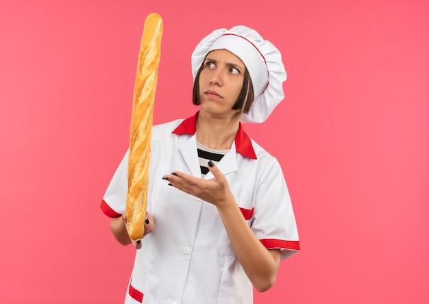 Zdezorientowana młoda kobieta kucharz w mundurze szefa kuchni, trzymając patrząc i wskazując ręką na kij chleba na różowym tle z miejsca na kopię