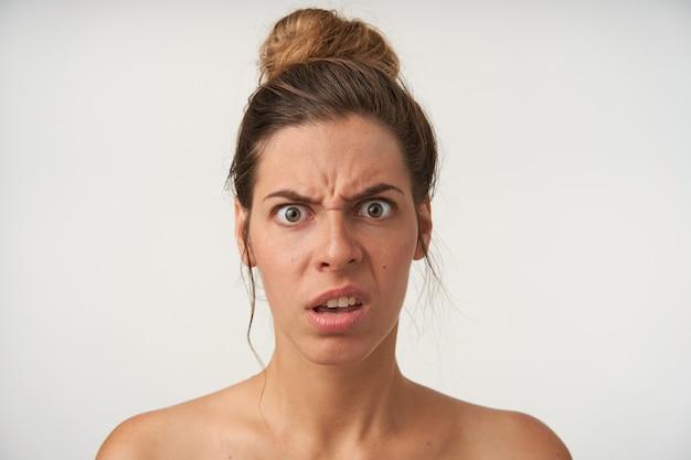 Zdezorientowana młoda kobieta pozująca z szeroko otwartymi oczami, marszcząca brwi i grymas, z fryzurą w kok i bez makijażu