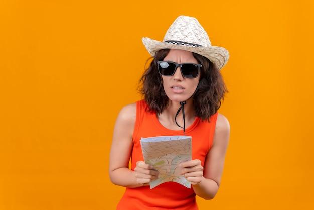 Zdezorientowana młoda kobieta z krótkimi włosami w pomarańczowej koszuli w kapeluszu przeciwsłonecznym i okularach przeciwsłonecznych, trzymając mapę
