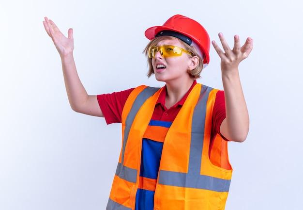 Zdezorientowana młoda konstruktorka w mundurze w okularach podnosząca ręce odizolowana na białej ścianie