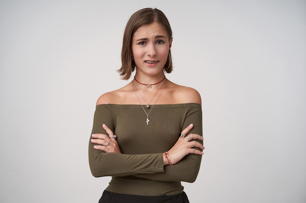 Zdezorientowana młoda, krótkowłosa brunetka kobieta krzyżuje ręce na klatce piersiowej, patrząc zdezorientowana z przodu, odizolowana na białej ścianie w zwykłych ubraniach